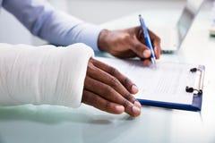 Formulario de demanda de relleno herido de seguro del hombre imagen de archivo