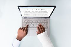 Formulario de demanda de relleno de seguro de With Bandage Hand del hombre de negocios fotografía de archivo libre de regalías