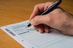Formulario de impuesto alemán - hombres que completan formulario de impuesto alemán de la pluma negra fotos de archivo libres de regalías