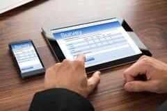 Formulario de la encuesta sobre el relleno del hombre de negocios Imagen de archivo libre de regalías