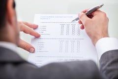 Formulario de relleno de la encuesta a los clientes del hombre de negocios Fotos de archivo libres de regalías