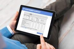 Formulario de relleno de la encuesta a los clientes del hombre en la tableta fotos de archivo