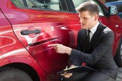 Formulario de relleno del seguro del hombre cerca del coche da?ado fotos de archivo libres de regalías