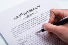Formulario de relleno de la denuncia del acoso sexual de la mano humana imagen de archivo