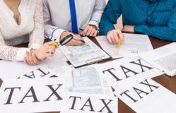 Formulario de relleno 1040 de los impuestos con ayuda del consejero fotografía de archivo