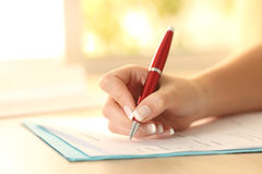 Formulario del relleno de la mano de la mujer en una tabla fotografía de archivo libre de regalías