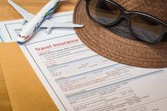 Formulario y sombrero de inscripción de la demanda de seguro del viaje con la lente encendido Fotos de archivo