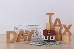 Formulera SKATTDAGEN, träkuber, husmodellen, kalendern och pengar på tabellen mot ljus bakgrund royaltyfri foto