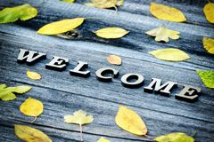 Formulera välkomnandet på en träbakgrund, ramen av gula sidor Arkivfoton