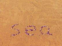 formuleringar & x22; sea& x22; bokstav på stranden Arkivbilder