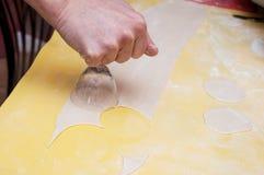 Formung von freien Räumen von einem Teig für selbst gemachtes pelmeni durch die Hände lizenzfreies stockfoto