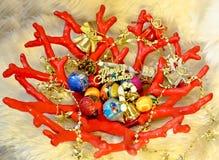 Formvase der roten Koralle mit Mehrfarbenweihnachtsbällen, kleinen Glocken und Girlande mit goldenen Sternen auf Schafpelzhinterg Stockbild