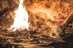fornace del fabbro con i carboni brucianti, gli strumenti ed i pezzi in lavorazione caldi d'ardore del metallo Immagini Stock