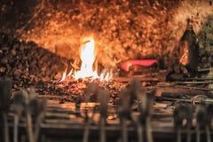 fornace del fabbro con i carboni brucianti, gli strumenti ed i pezzi in lavorazione caldi d'ardore del metallo Immagine Stock Libera da Diritti