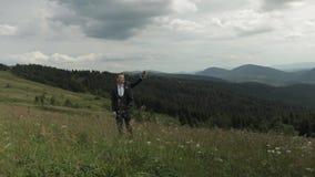 Fornal, brunetka młodego człowieka pobyt na wierzchołku góry Podnosi jego rękę w górę zbiory