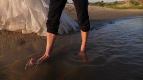 Fornal jest bosy i panna młoda w białej sukni chodzi wzdłuż rzeki wzdłuż wody para w miłości chodzi na zbiory wideo