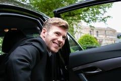 Fornal przyjeżdża samochodem przy wioska kościół na jego dniu ślubu obrazy stock