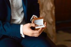 Fornal trzyma pudełko z obrączkami ślubnymi przed ślubną ceremonią Mężczyzna ręki trzyma pudełko z pierścionkami fotografia stock