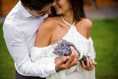 Fornal w białego koszulowego przytulenia uśmiechniętej pannie młodej w biel sukni z bukietem kwiaty Zdjęcia Royalty Free