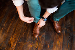 Fornal wiąże shoelaces w jego brown butach Fotografia Royalty Free