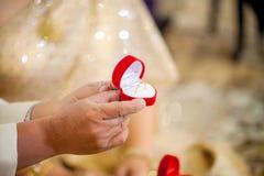 Fornala ` s ręki chwyta czerwieni pudełko pokazywać, obrączka ślubna Poślubiać i małżeństwa symbole panny młodej ceremonii kwiatu zdjęcie royalty free