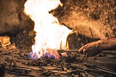 fornalha do ferreiro com carvões ardentes, ferramentas, e os workpieces quentes de incandescência do metal fotos de stock royalty free