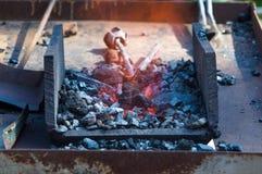 fornalha do ferreiro com carvões ardentes, ferramentas, e os workpieces quentes de incandescência do metal imagens de stock royalty free