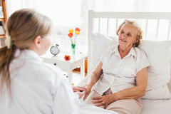 Fornecendo o cuidado para pessoas idosas Doutor que visita o paciente idoso em casa imagens de stock