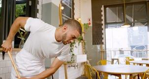 Fornisca la pulizia di personale del pavimento in un caffè 4k video d archivio