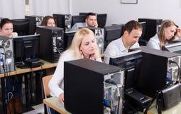 Fornisca la seduta agli scrittori e l'esame di personale degli schermi del PC Immagini Stock Libere da Diritti
