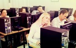 Fornisca la seduta agli scrittori e l'esame di personale degli schermi del PC Immagini Stock