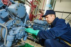 Fornisca un servizio al lavoratore alla stazione industriale del compressore Fotografie Stock