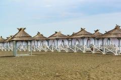 Fornito di tende con i tetti ricoperti di paglia e le tende bianche ha abbandonato la spiaggia un giorno nuvoloso Il fuori stagio Fotografie Stock Libere da Diritti