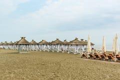 Fornito di tende con i tetti ricoperti di paglia, spiaggia abbandonata un giorno nuvoloso Fotografie Stock