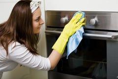 Forno da limpeza da limpeza da dona de casa no kitche Fotos de Stock Royalty Free