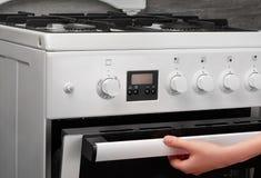 Forno fêmea da abertura da mão no fogão de gás branco da cozinha Imagem de Stock Royalty Free