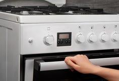 Forno fêmea da abertura da mão no fogão de gás branco da cozinha Fotografia de Stock Royalty Free