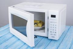 Forno micro-ondas branco, em uma superfície de madeira azul para o alimento de aquecimento Foto de Stock Royalty Free