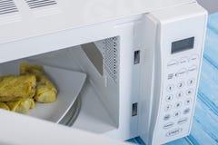 Forno micro-ondas branco, em uma superfície de madeira azul para o alimento de aquecimento Fotografia de Stock Royalty Free