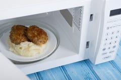 Forno micro-ondas branco, em uma superfície de madeira azul para o alimento de aquecimento Fotos de Stock