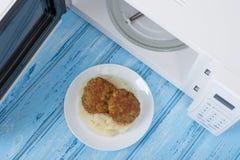 Forno micro-ondas branco, em uma superfície de madeira azul para o alimento de aquecimento Fotos de Stock Royalty Free