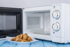 Forno micro-ondas branco, em uma superfície de madeira azul para o alimento de aquecimento Imagem de Stock Royalty Free