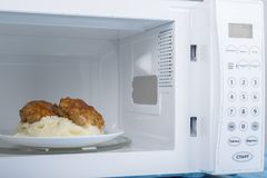 Forno micro-ondas branco, em uma superfície de madeira azul para o alimento de aquecimento Imagens de Stock Royalty Free