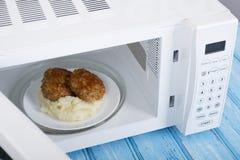 Forno micro-ondas branco, em uma superfície de madeira azul para o alimento de aquecimento Imagens de Stock