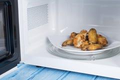 Forno micro-ondas branco, em uma superfície de madeira azul para o alimento de aquecimento Imagem de Stock