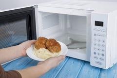 Forno micro-ondas branco, em uma superfície de madeira azul para o alimento de aquecimento Foto de Stock