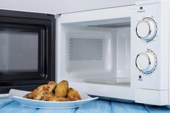 Forno micro-ondas branco, em uma superfície de madeira azul para o alimento de aquecimento Fotografia de Stock