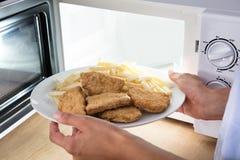Forno micro-ondas de Person Heating Fried Food In fotografia de stock royalty free