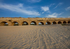 Forntida akvedukt mellan sand och himlar Arkivfoto