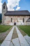 Forntida alpin kyrka med frescoed yttre väggar royaltyfria foton